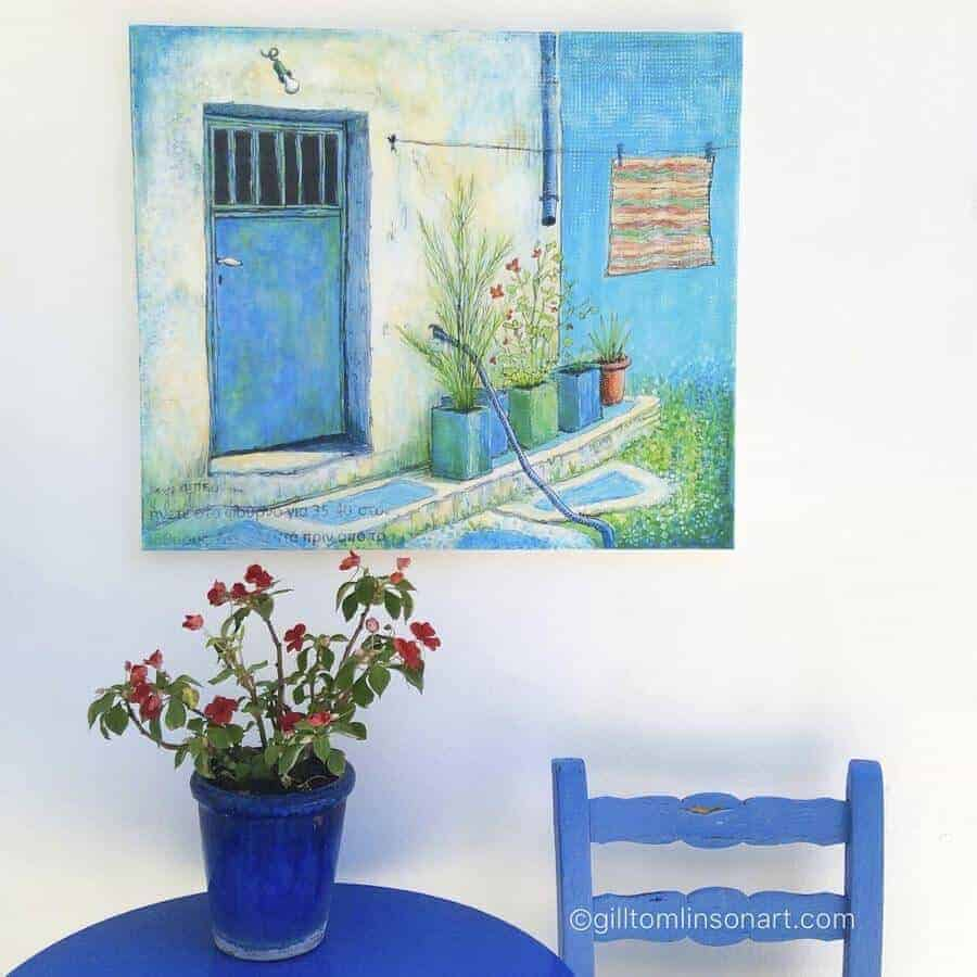 Painting of a Greek village courtyard with blue door and flower pots and rag rug by Gill Tomlinson