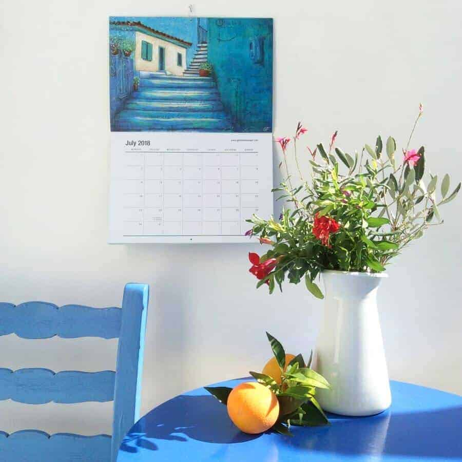 July calendar image with blue chair table and flowers and oranges